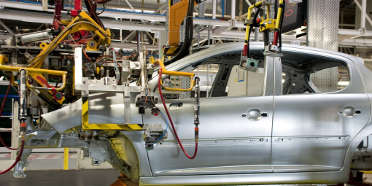 Car with aluminum and steel parts being assembled at manufacturing plant