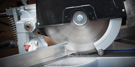 A saw cutting an aluminum extrusion