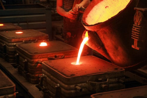 Operator pouring molten metal into a sand cast mold